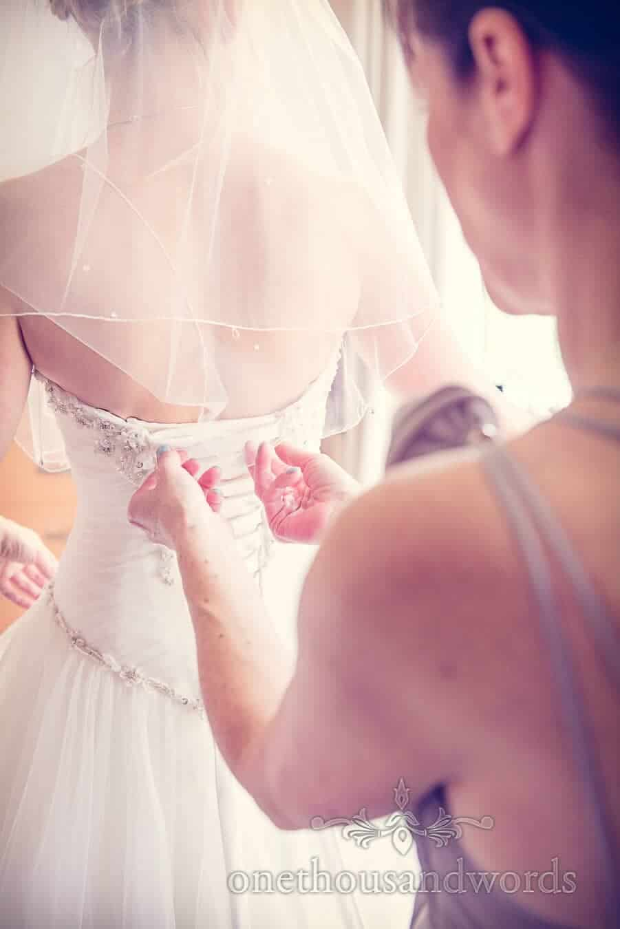 Detail photograph of lacing a wedding dress on wedding morning