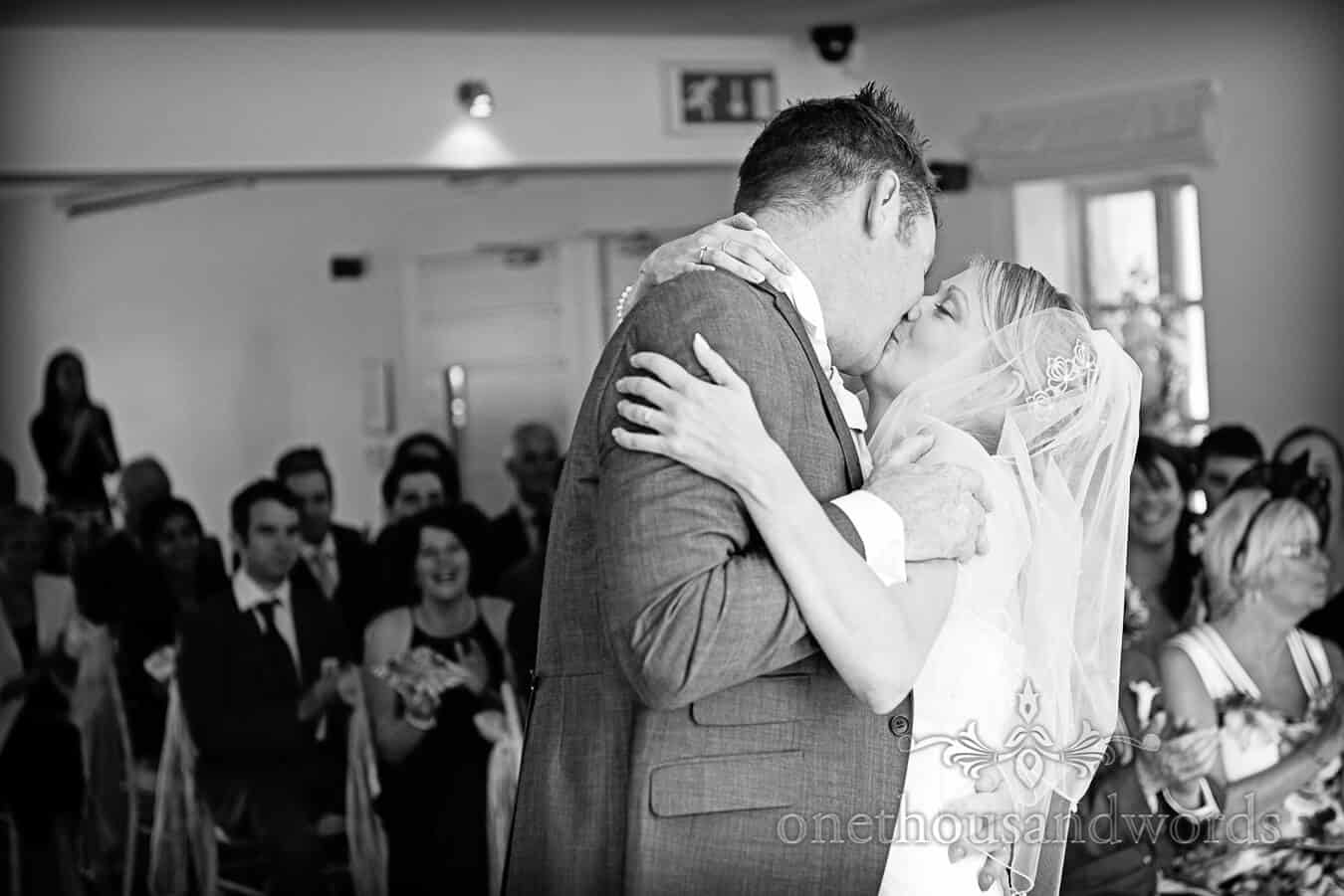 First kiss at Italian Villa Wedding ceremony in Dorset black and white photograph