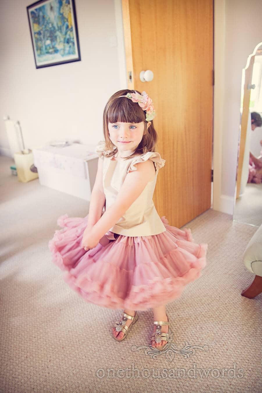 Flower girl in dusty pink flower girl skirt twirls