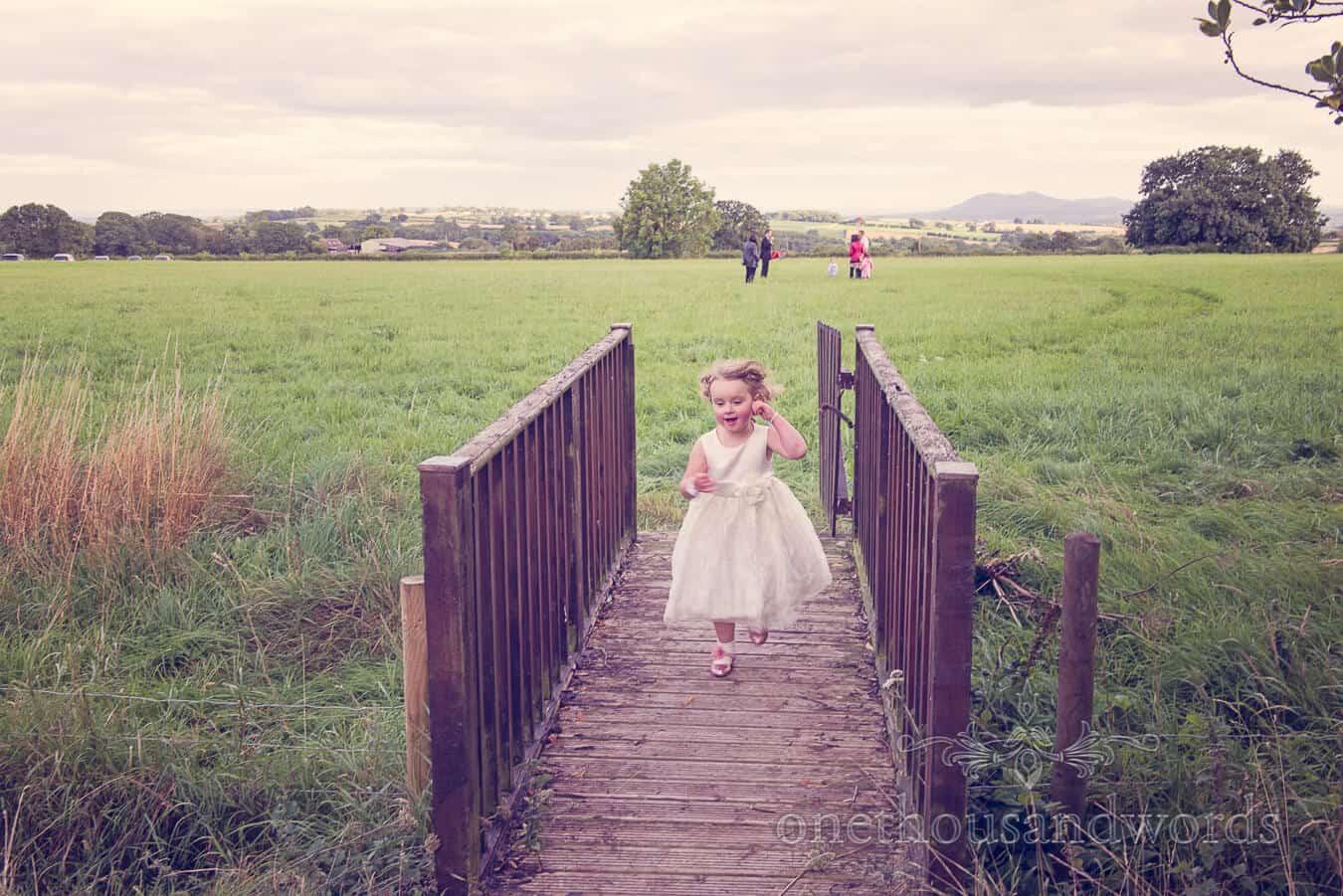Flower girl on wooden bridge at Countryside Wedding Photographs