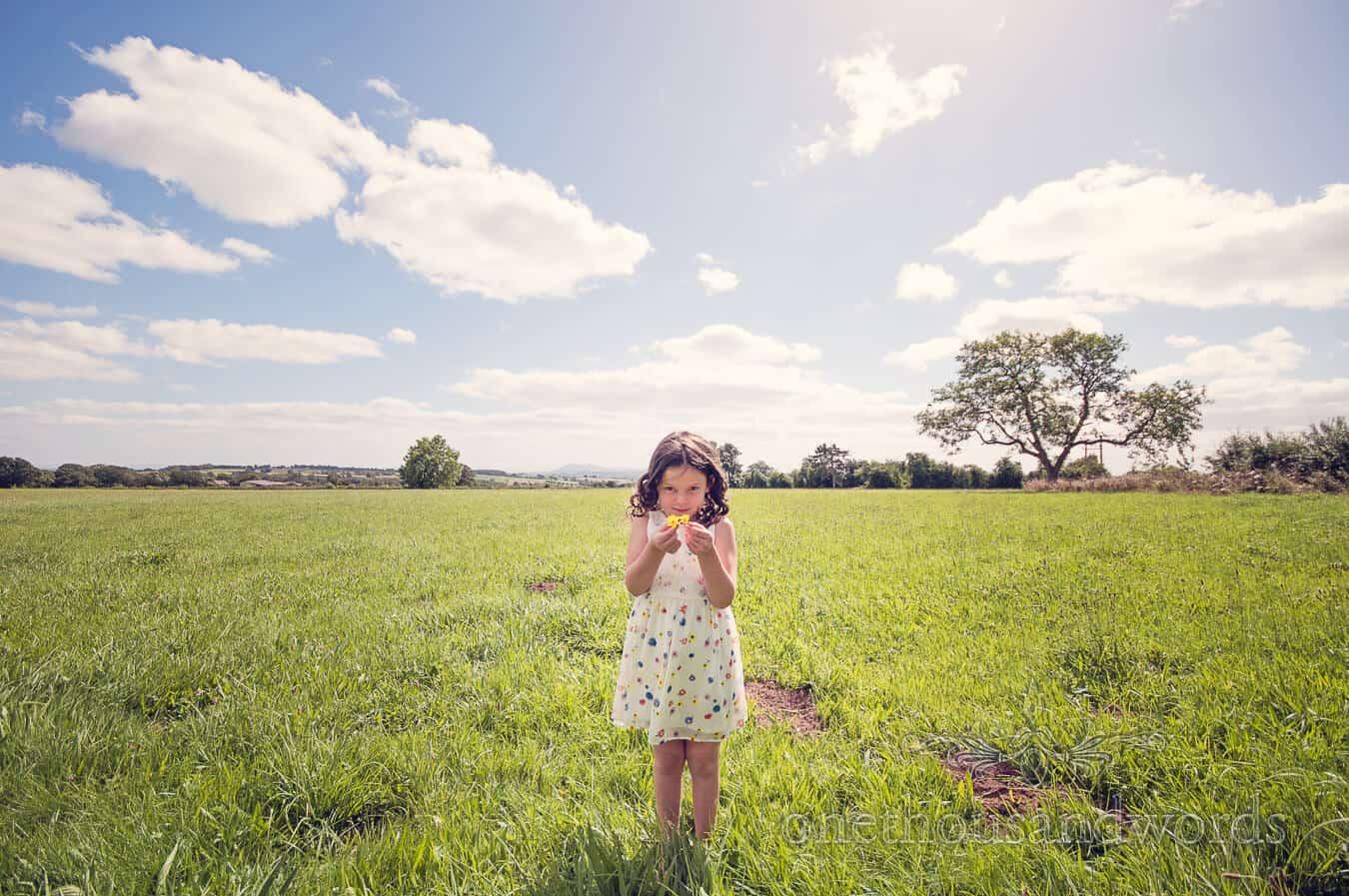 Flower girl picks flowers in field on morning of Countryside Wedding