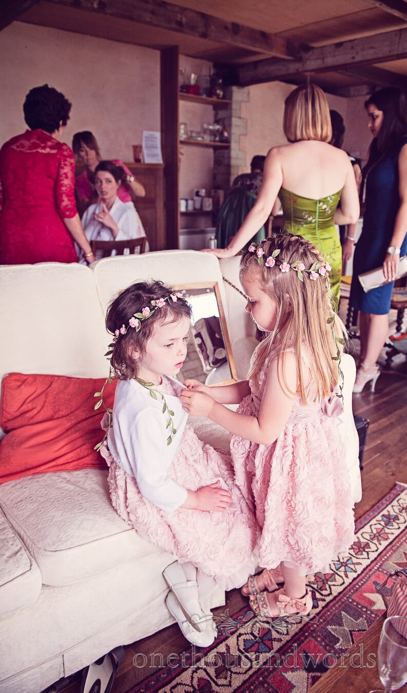Flower girls dress themselves in pink floral dresses on wedding morning