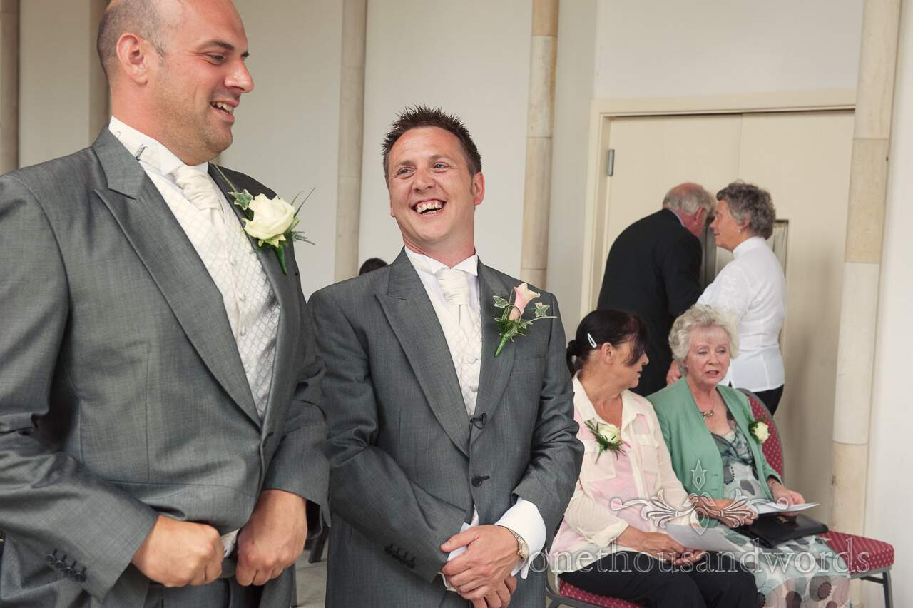 Groom and best man laughing at Highcliffe Castle wedding ceremony