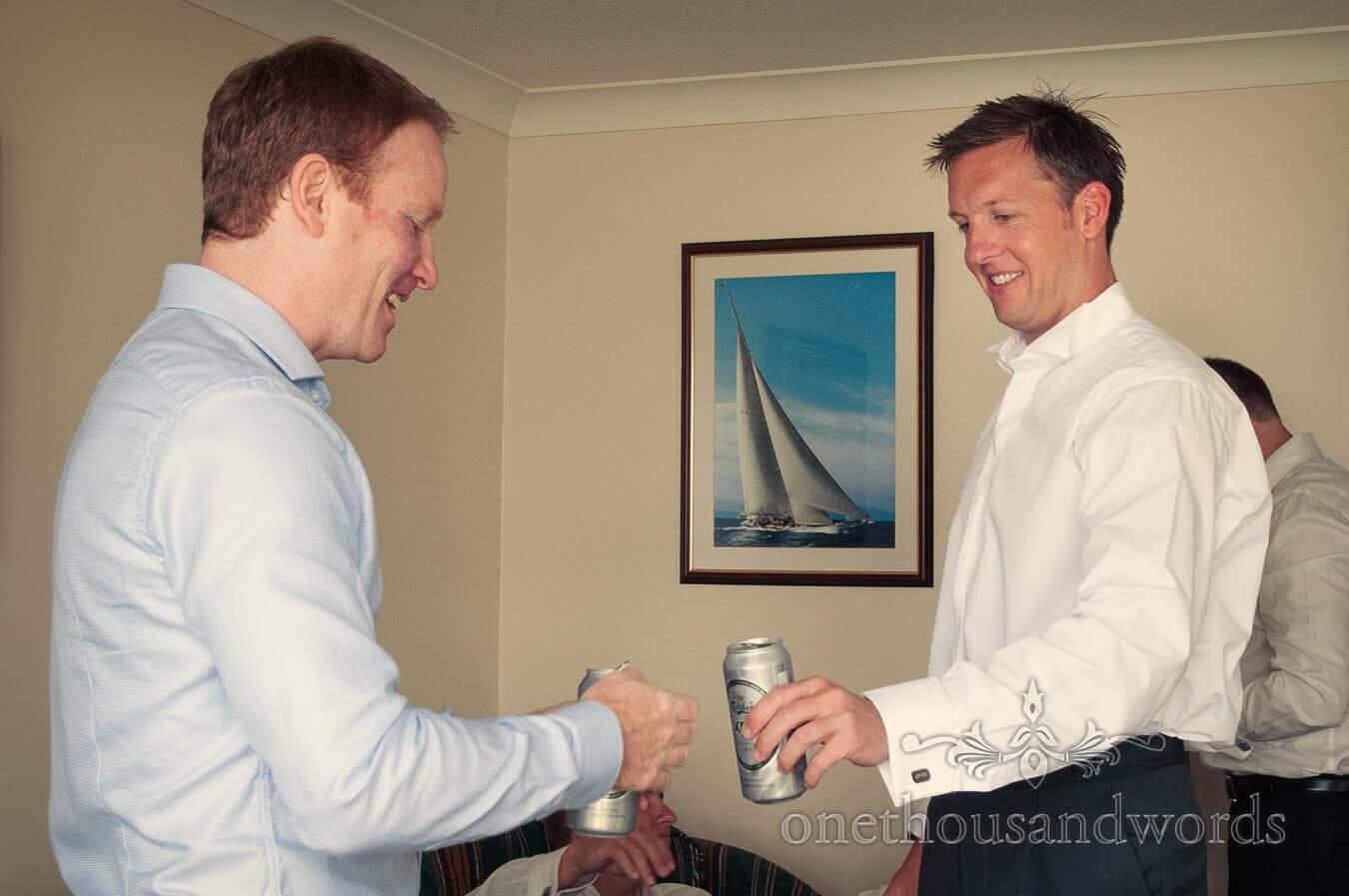 Groom and groomsman share a beer on wedding morning