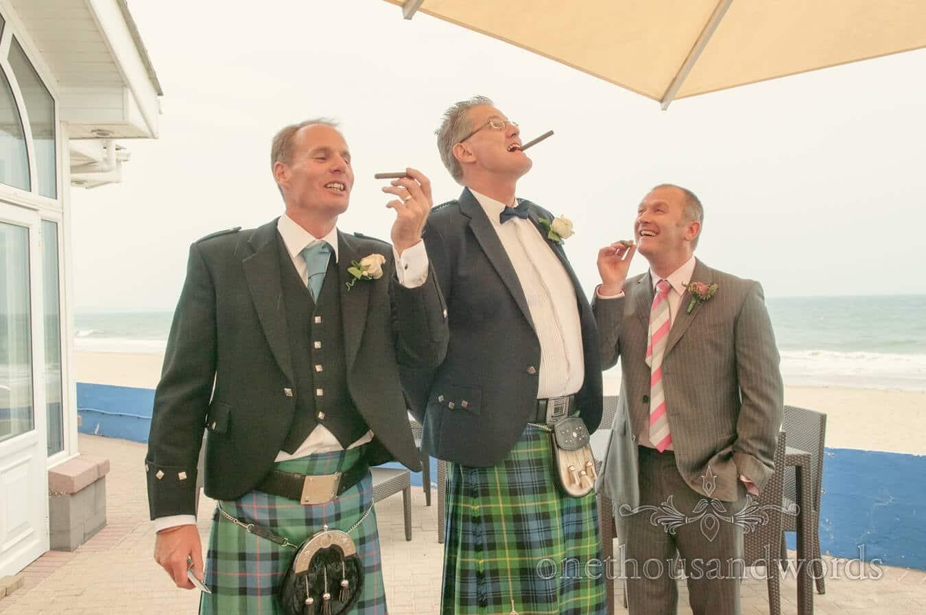 Groom and groomsmen in kits smoke cigars by the sea