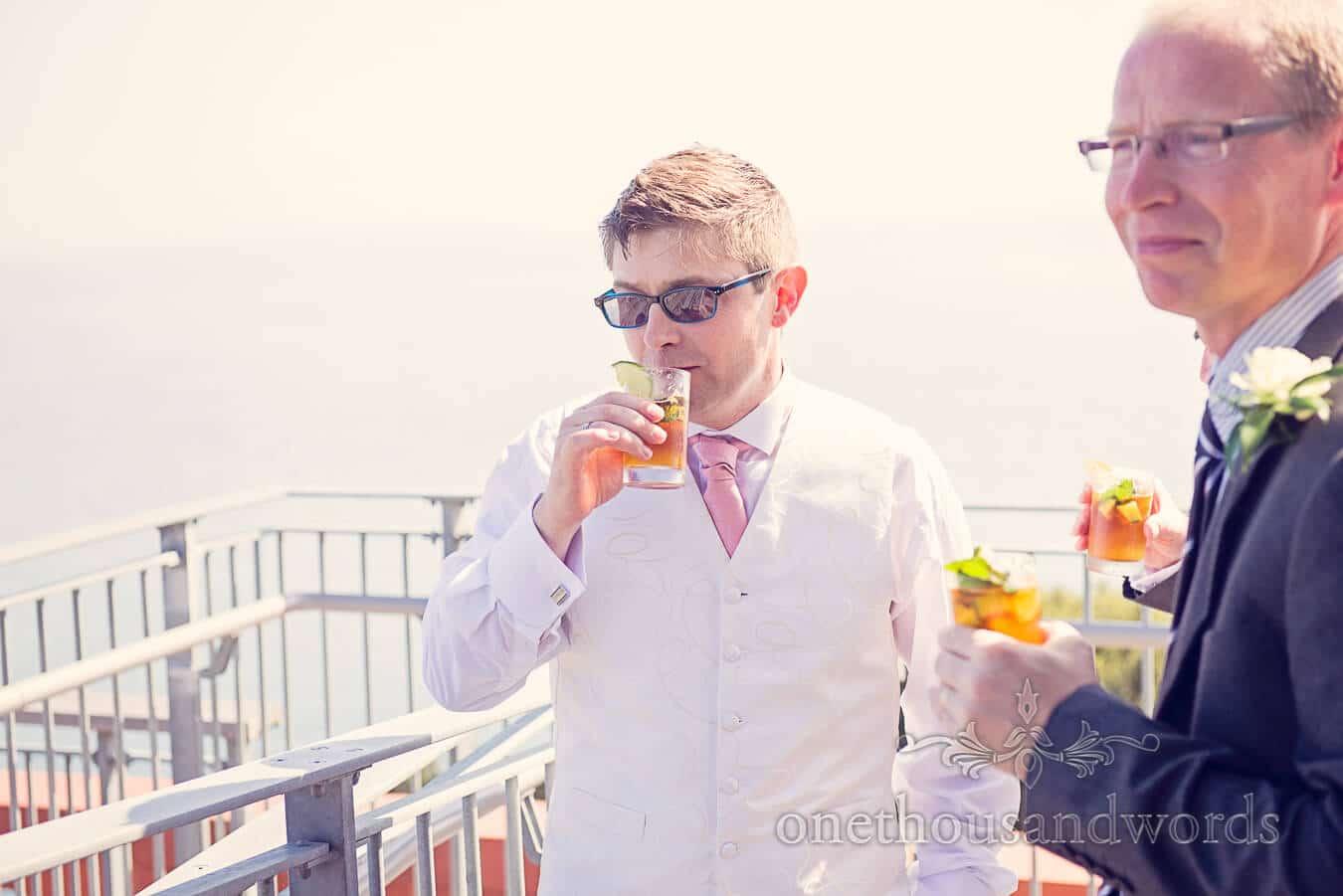 Groom Drinks Pims at seaside Wedding Drinks Reception