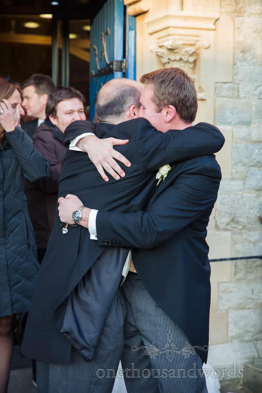 Groom hugs wedding guest at Hampton Court House