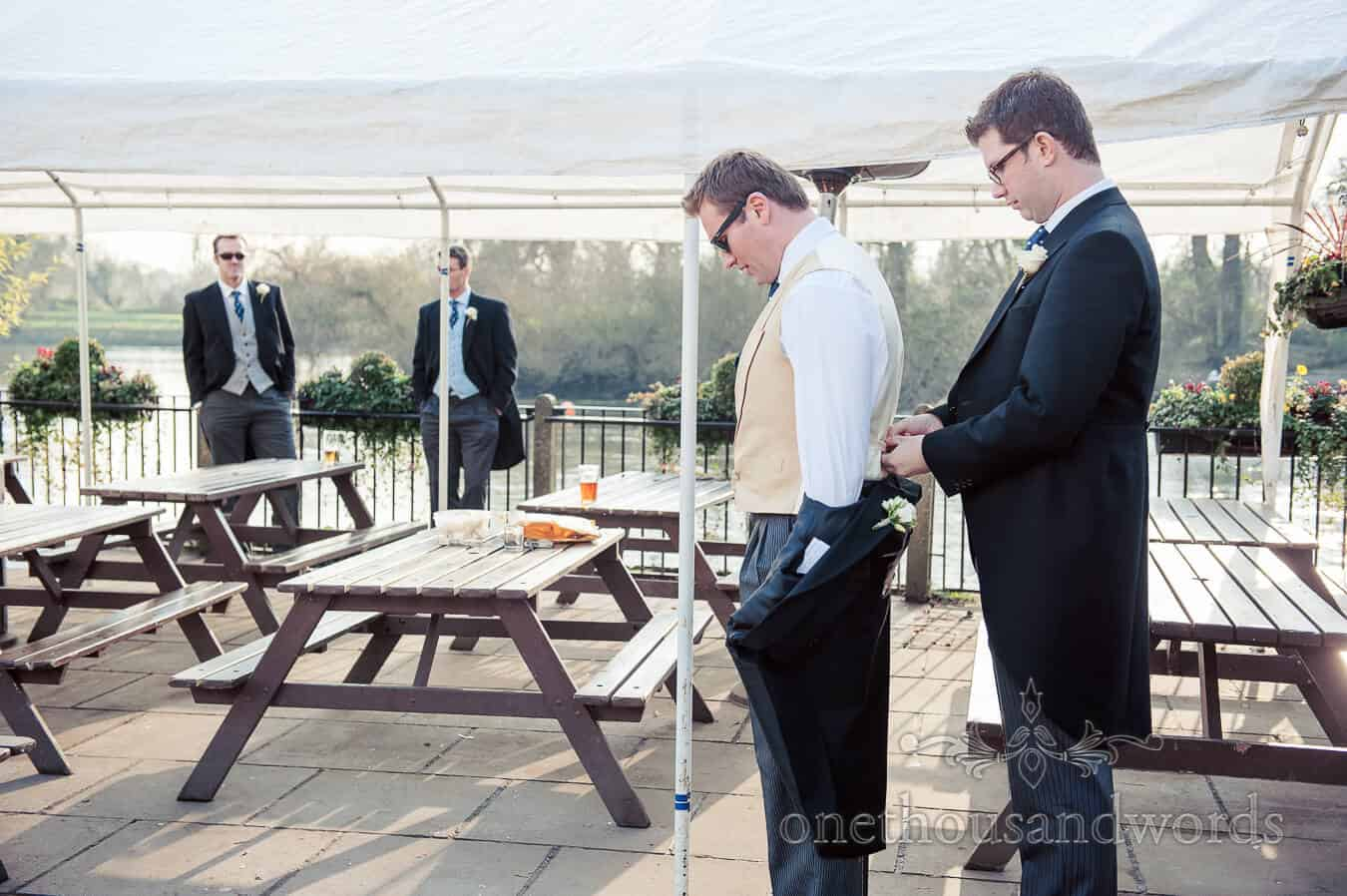 Groom is dressed by groomsman by the Thames on wedding morning