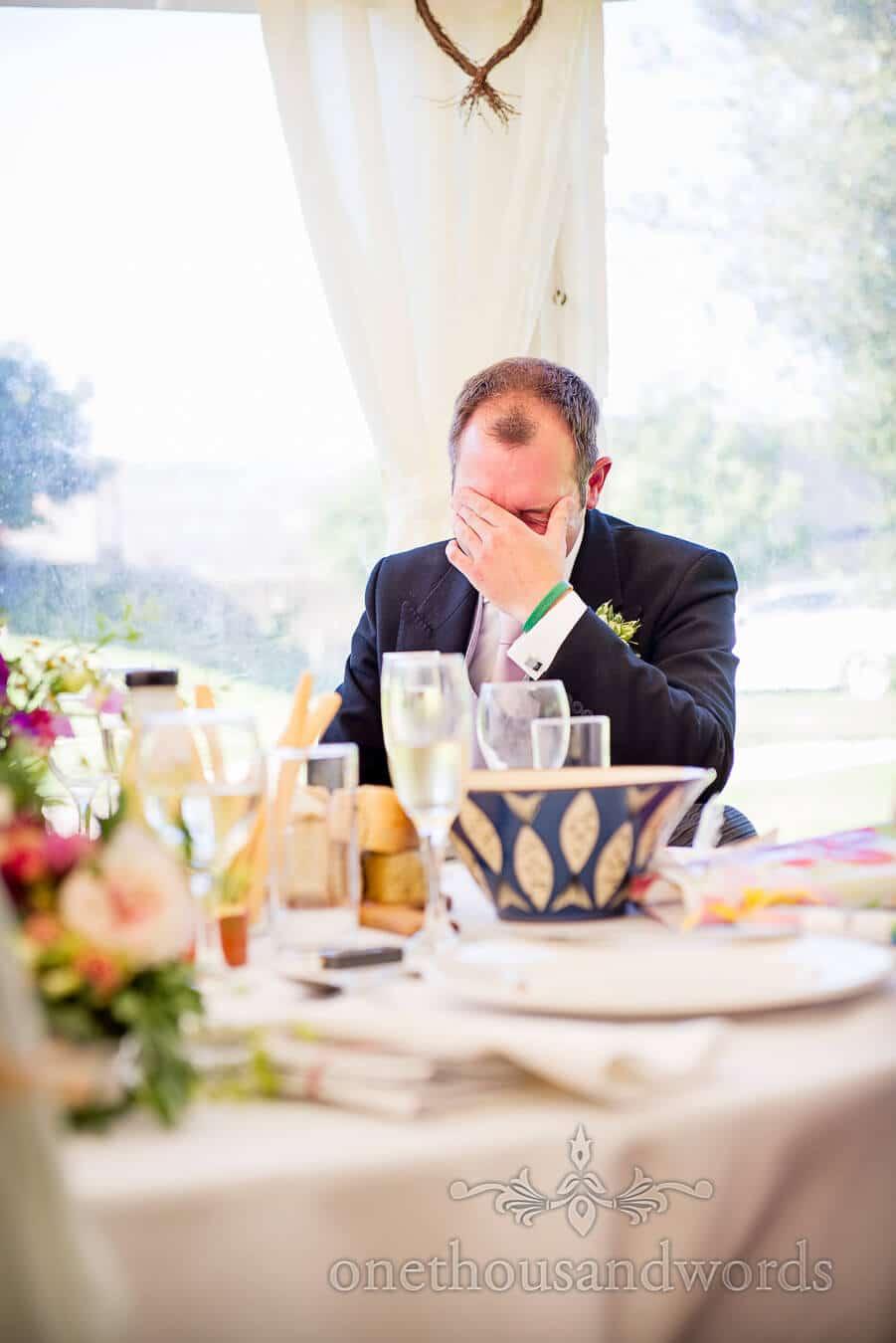 Groom reacts to best man's speech in wedding marquee