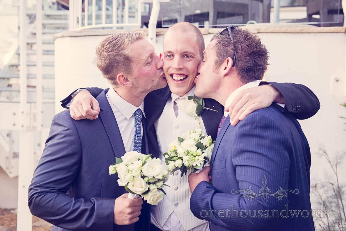 Groomsmen kiss the groom at Harbour Heights, Poole wedding venue