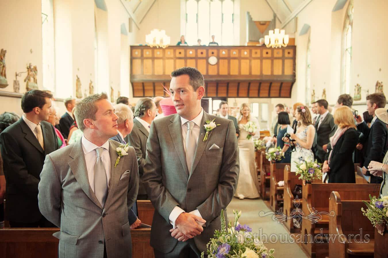 Grrom waits as bride walks down church aisle at Swanage wedding ceremony