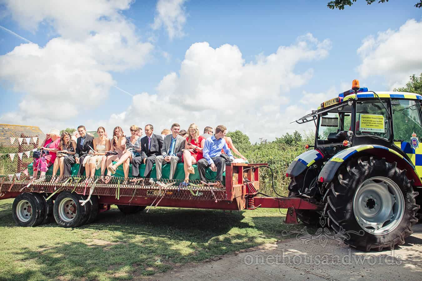 Guests sitting on wedding tractor trailer with police tractor