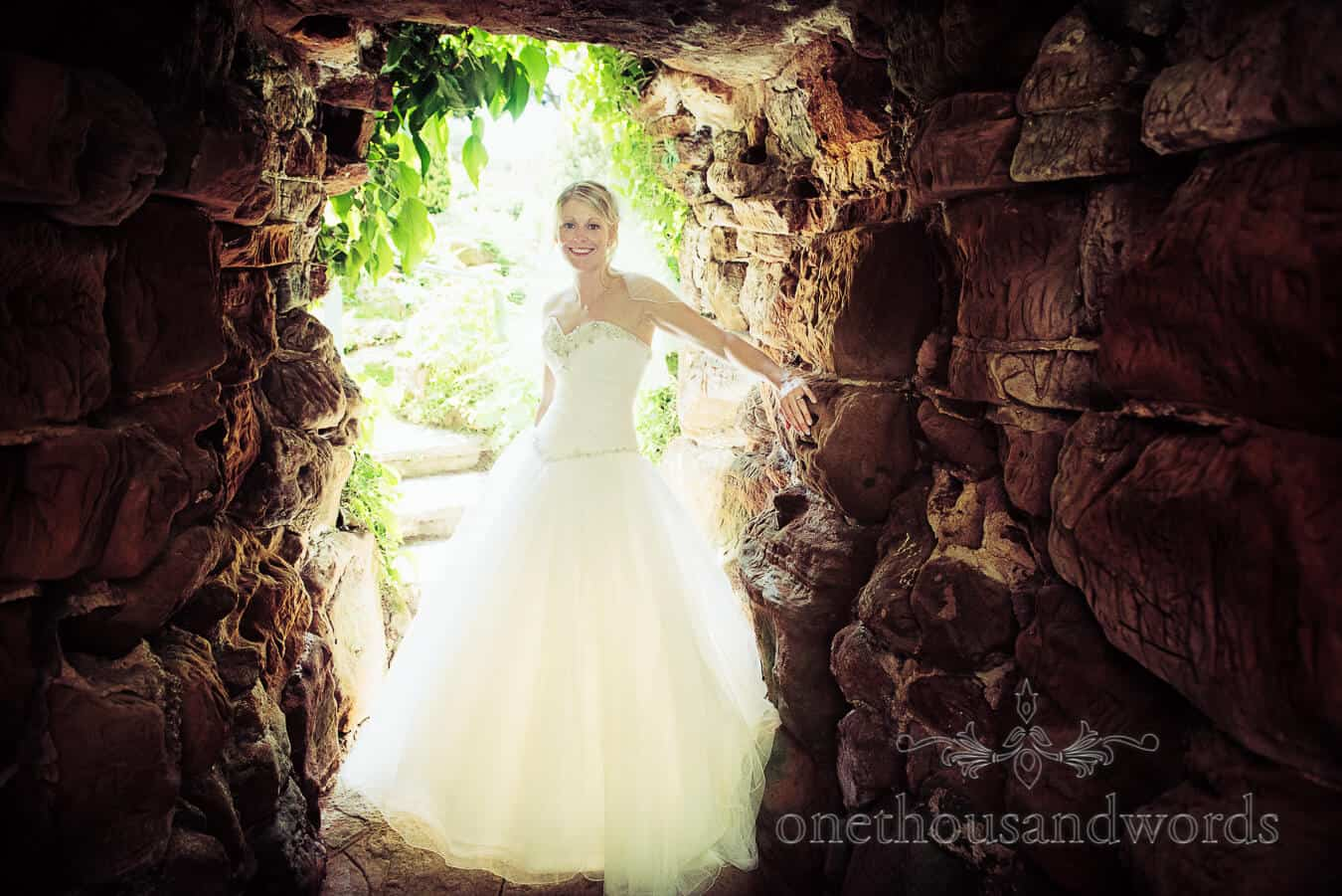 Happy bride in wedding dress sand stone tunnel at Italian Villa Wedding Photographs