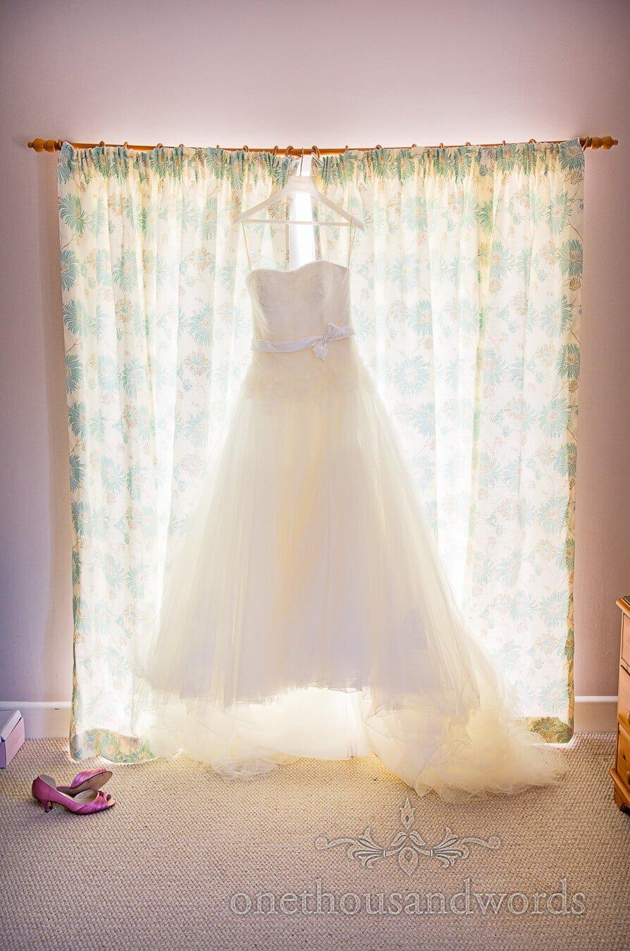 Lace wedding dress hanging on Dorset home wedding morning