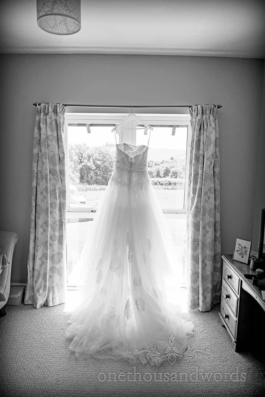 Lace wedding dress hangs in window on Dorset home wedding morning