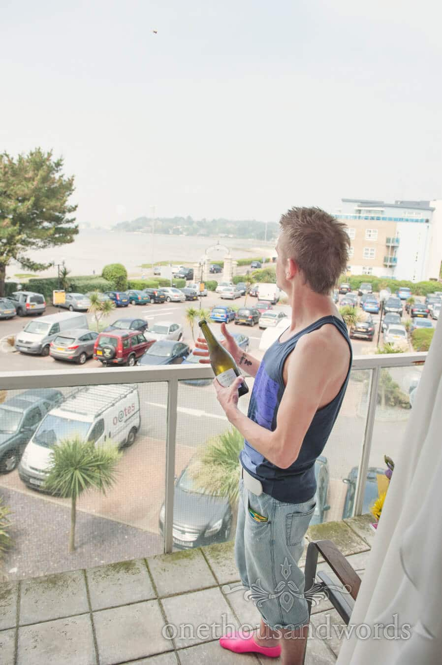 Male bridesmaid opens champagne over hotel balcony at Poole Harbour