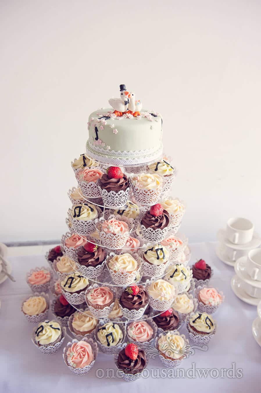 Musical wedding cake with cupcakes and swans