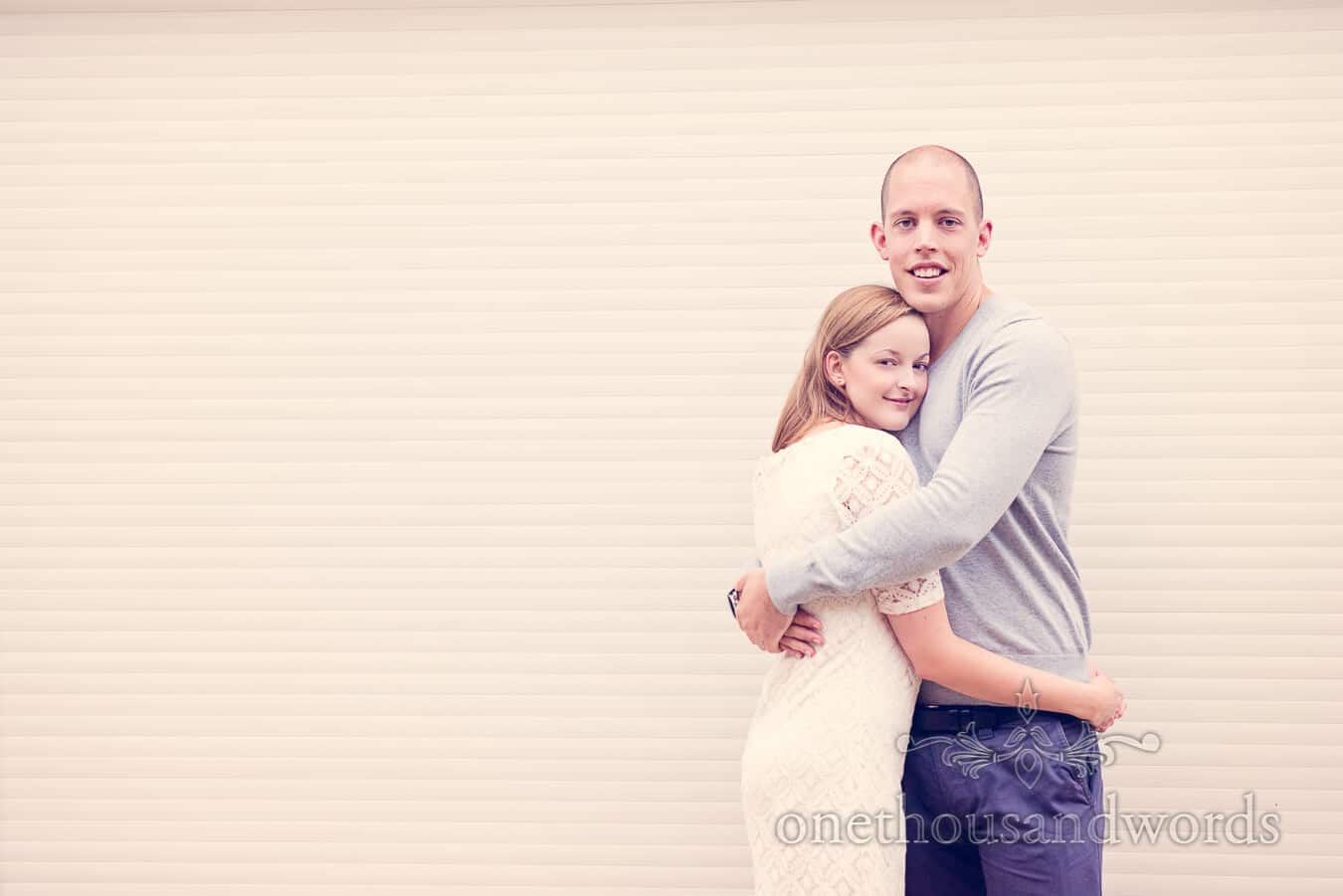 Bride and groom to be hug against white slatted backdrop