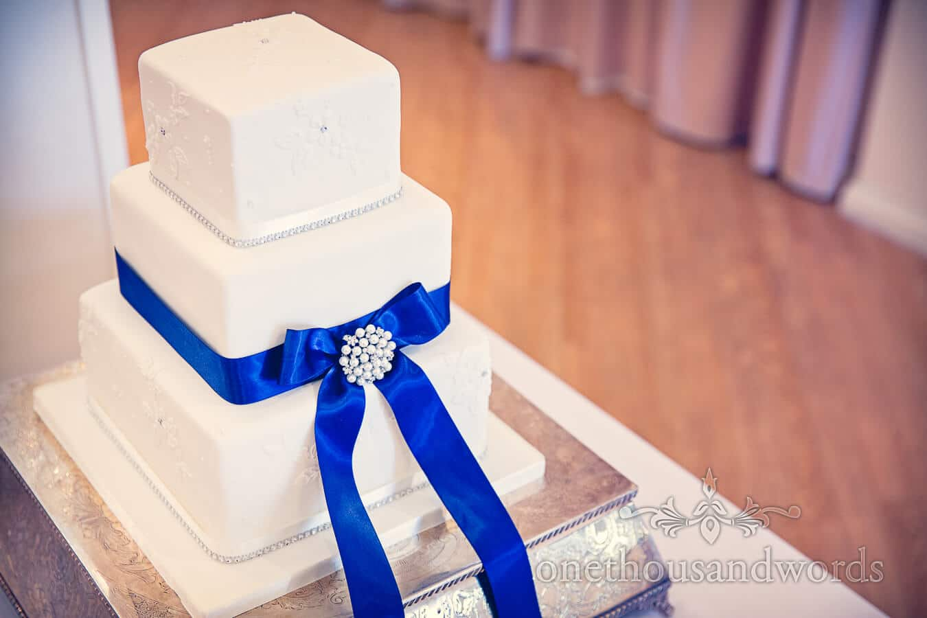 Three tier square wedding cake with blue ribbon at Salterns Hotel Wedding