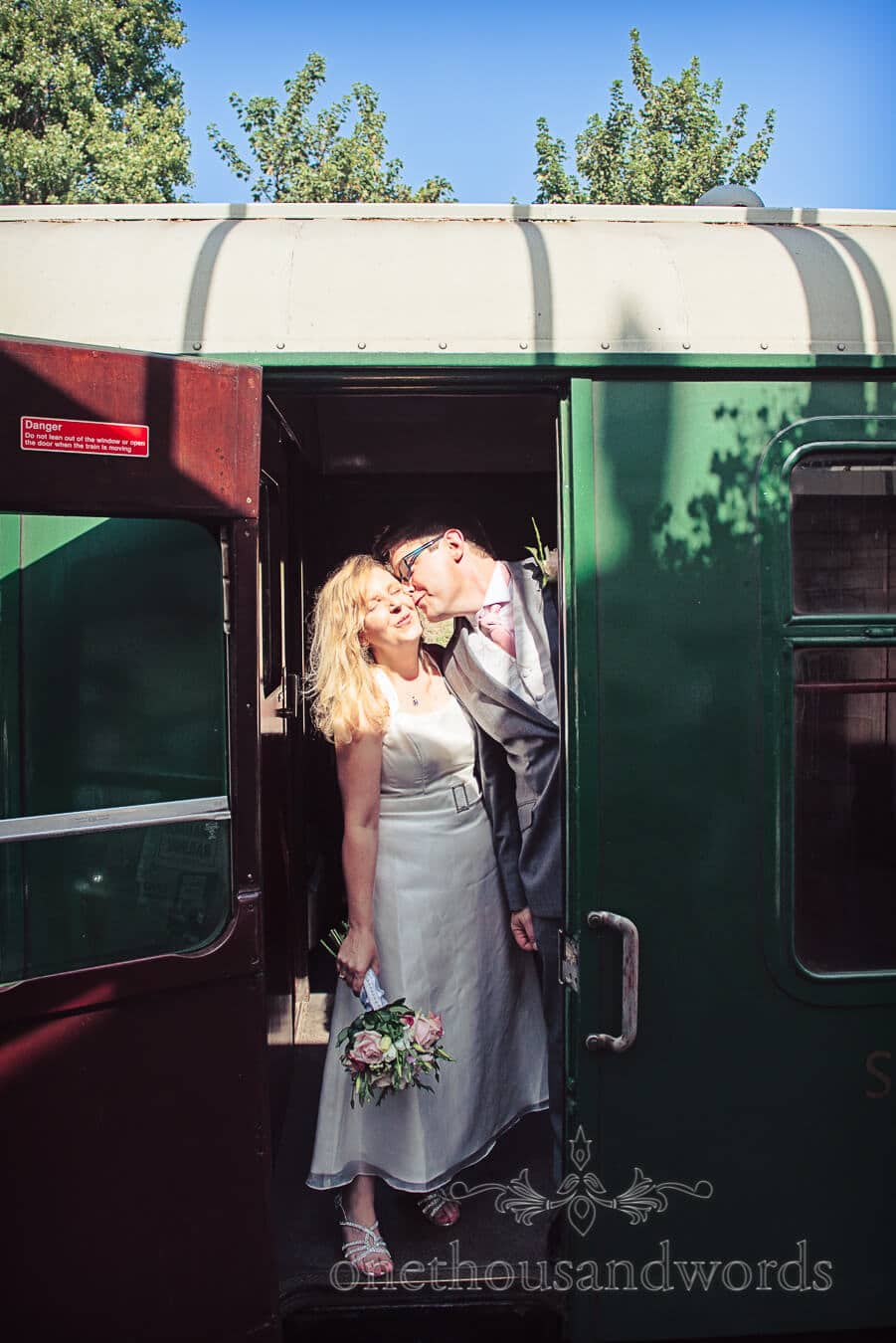 bride and groom kiss onboard green steam train