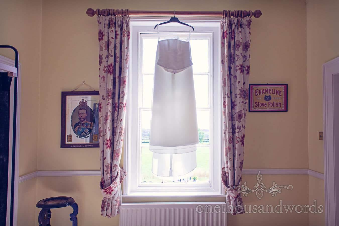 Weddign dress hangs in window on morning of Countryside Wedding photographs