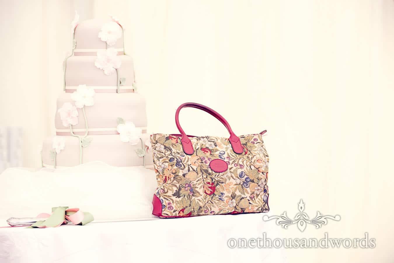 Wedding cake and floral handbag in wedding marquee