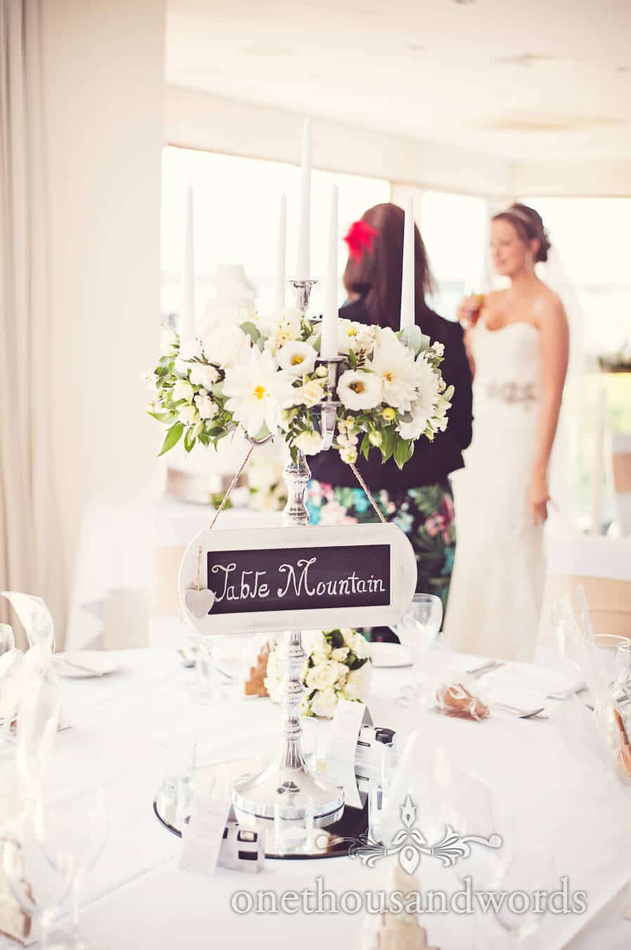 Wedding candelabra with wedding flowers and sign at Poole wedding venue