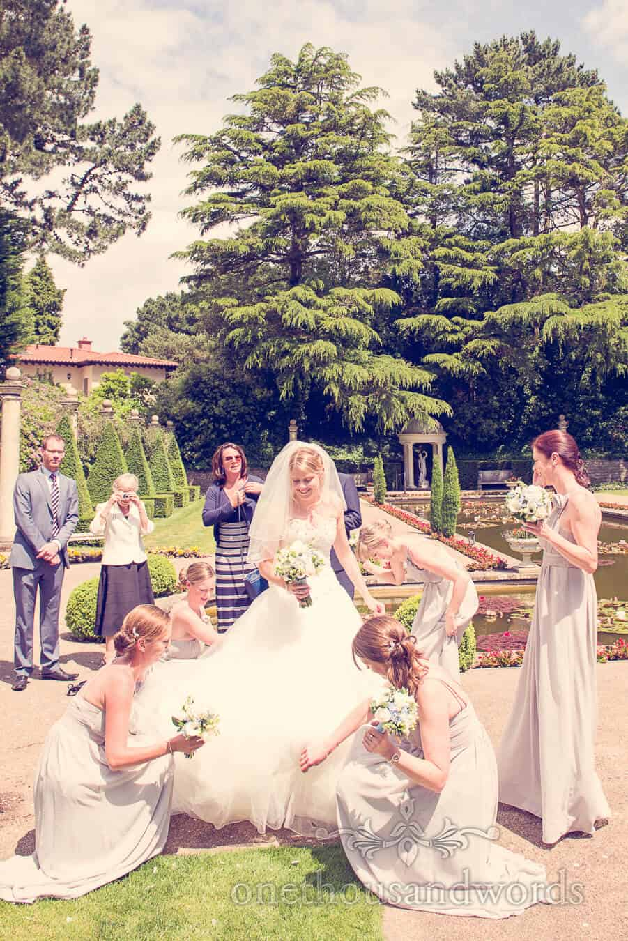 Wedding dress is adjusted by bridesmaids in gardens at Italian Villa Wedding