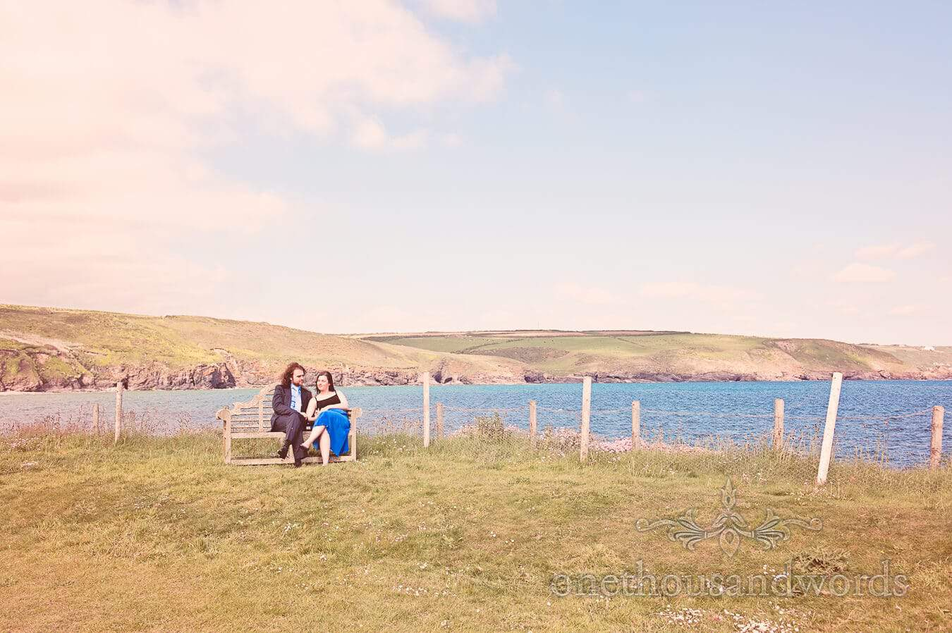 Wedding guests sit on bench by the sea at Prussia Cove, Cornwall