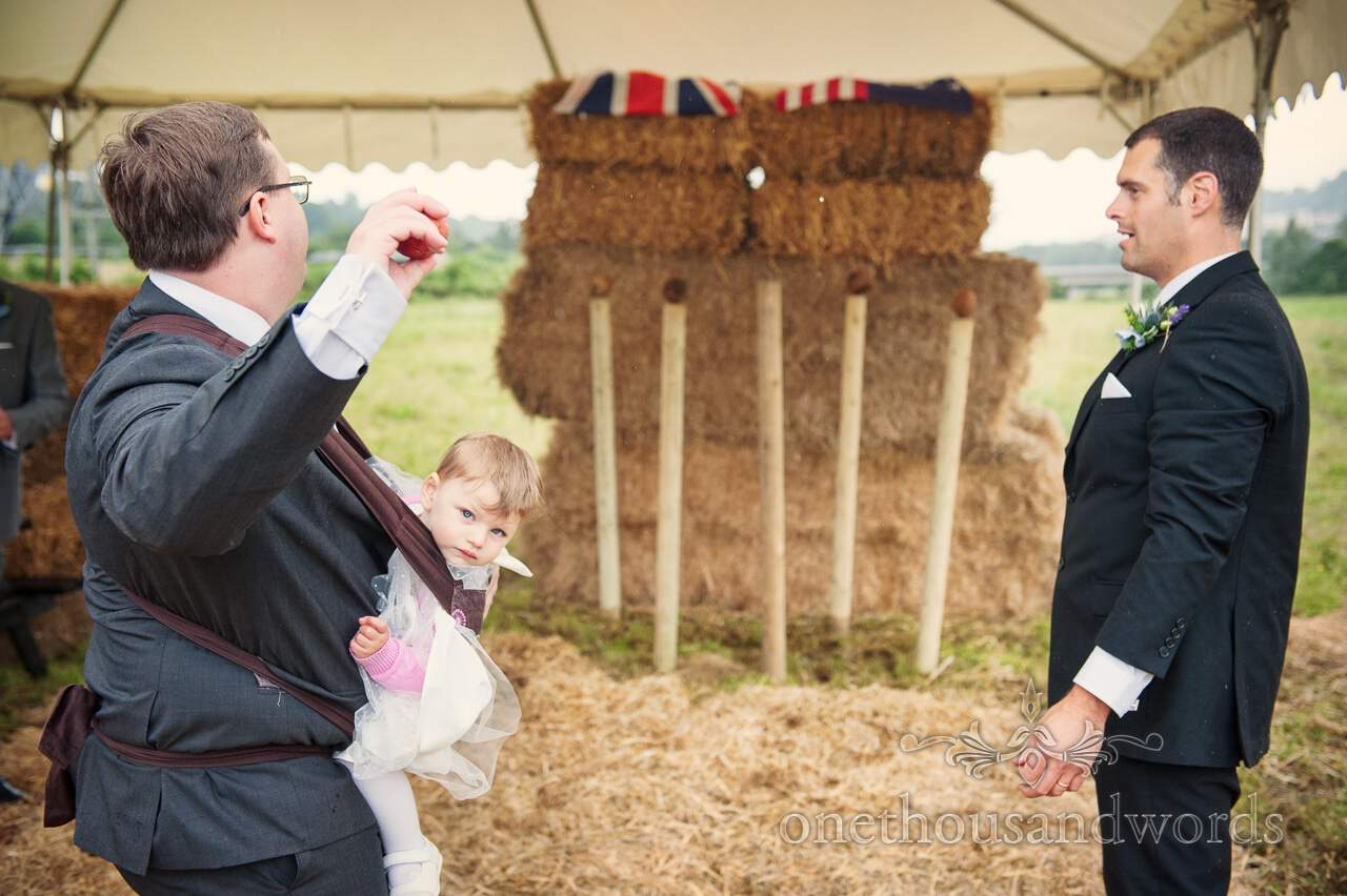 Wedding guests use coconut shy at wedding with child