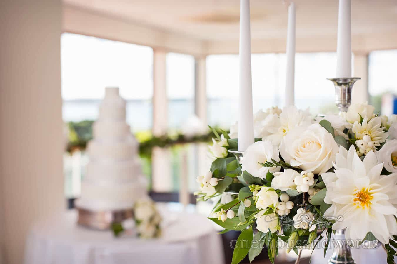 White wedding flower sprays with candles at Poole wedding venue