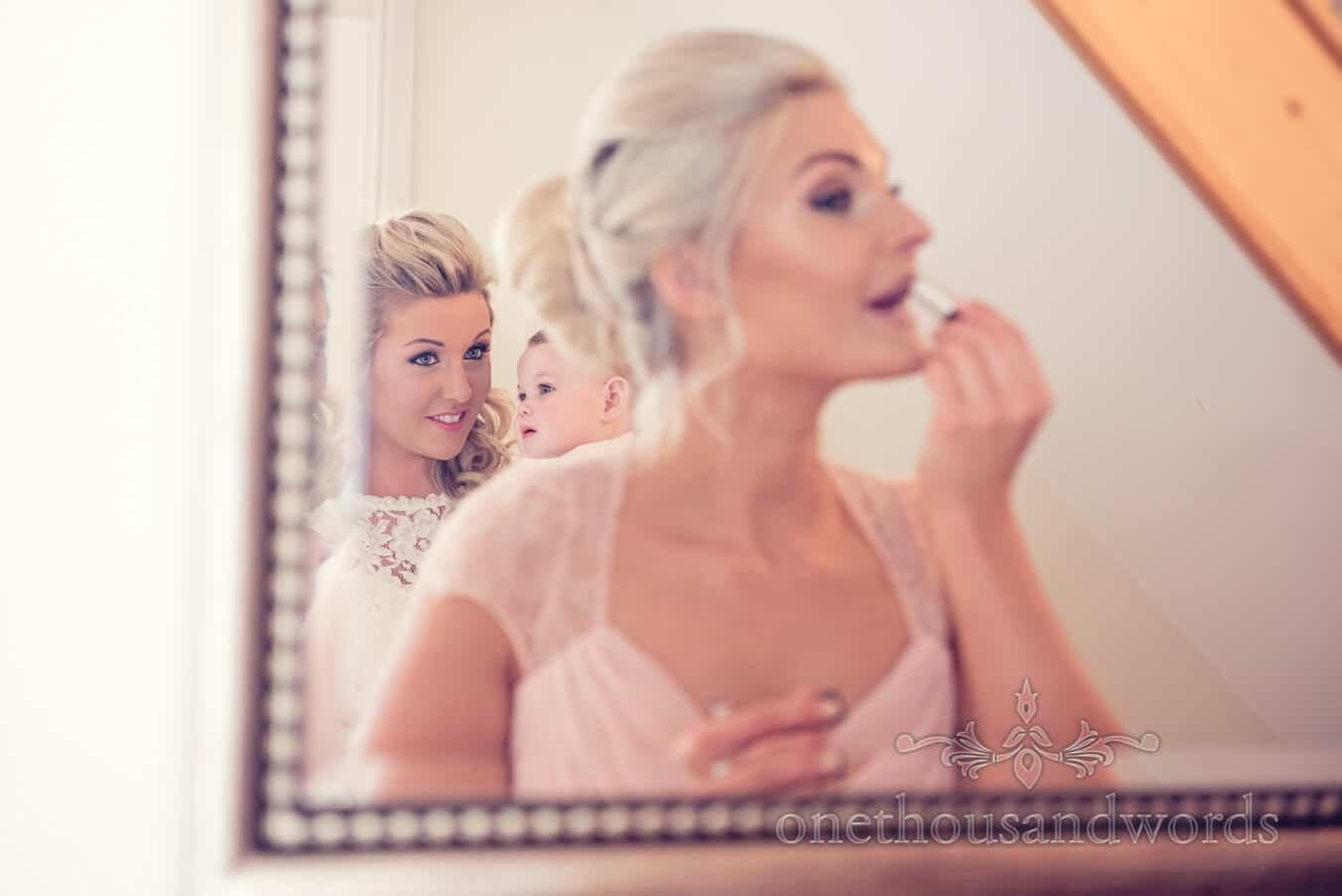 Bride, daughter and bridesmaid in mirror