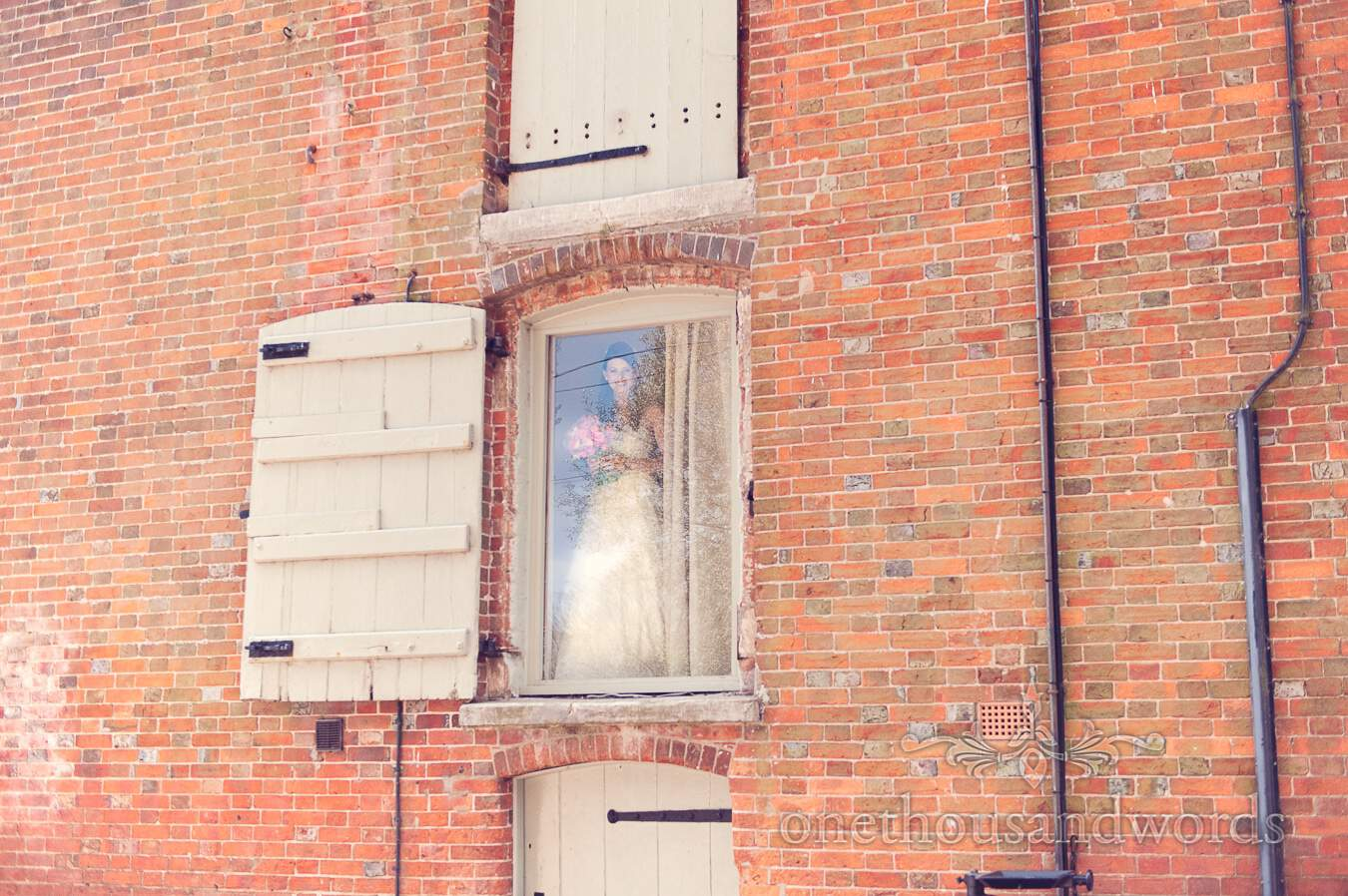 Bride in window before wedding at Sopley Mill