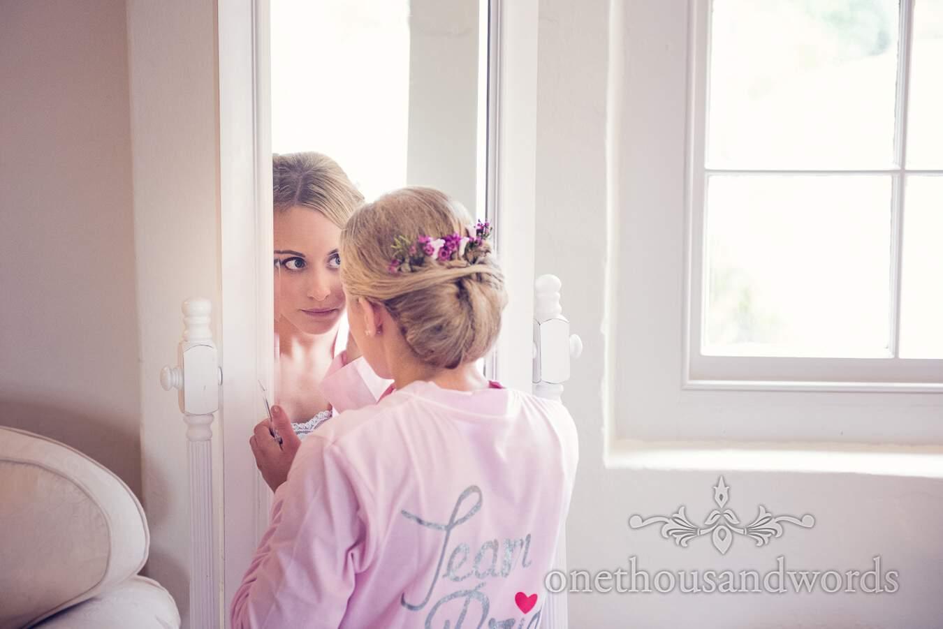 Bridesmaid in mirror before wedding at Sopley Mill