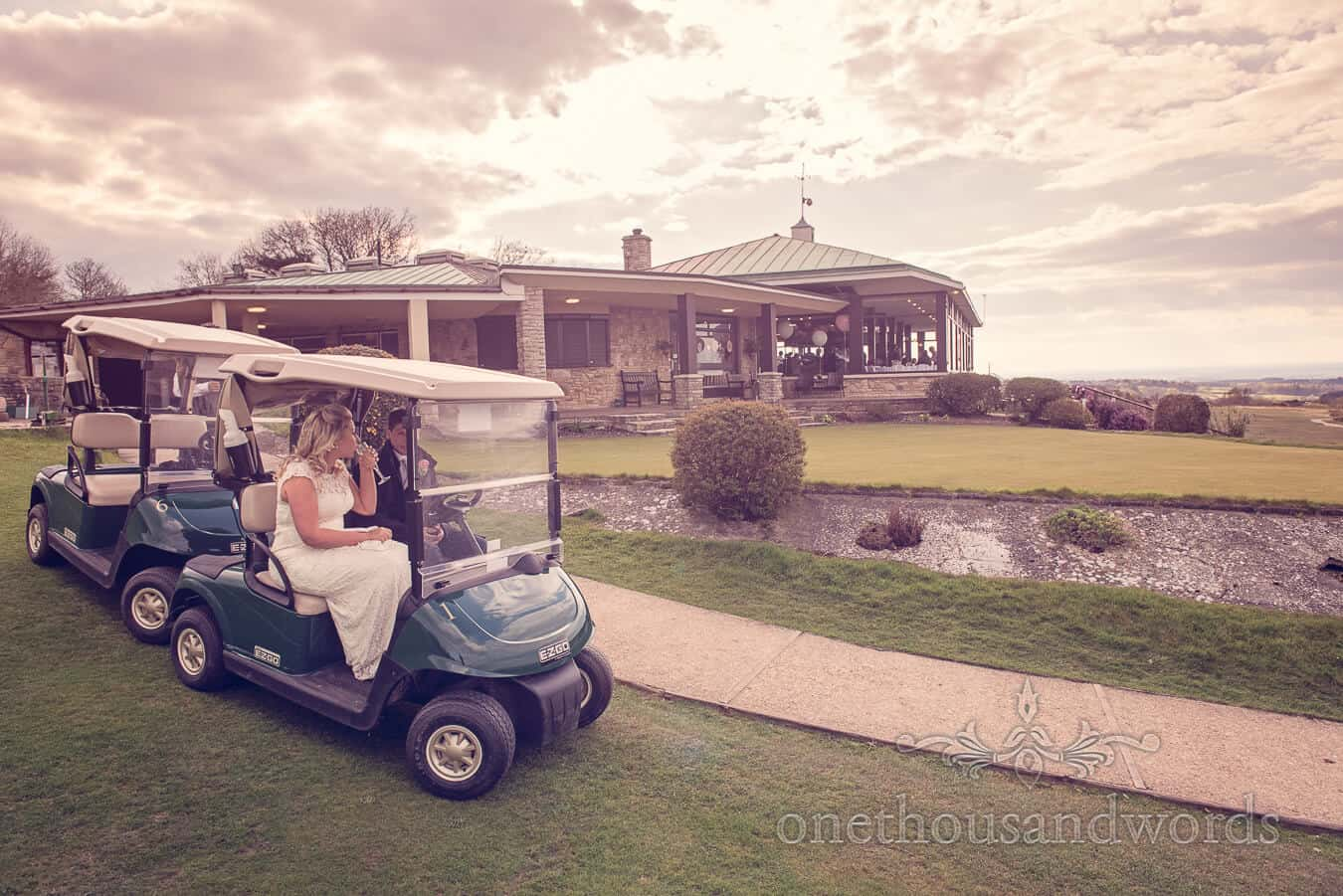 Couple in buggies in front of clubhouse at Purbeck Golf Club Wedding