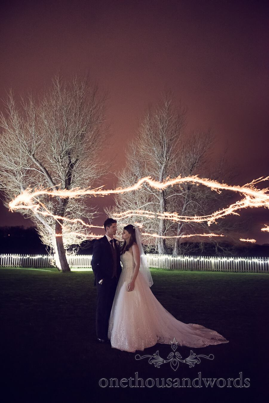 Couple in garden with sparkler trails from wedding at Sopley Mill