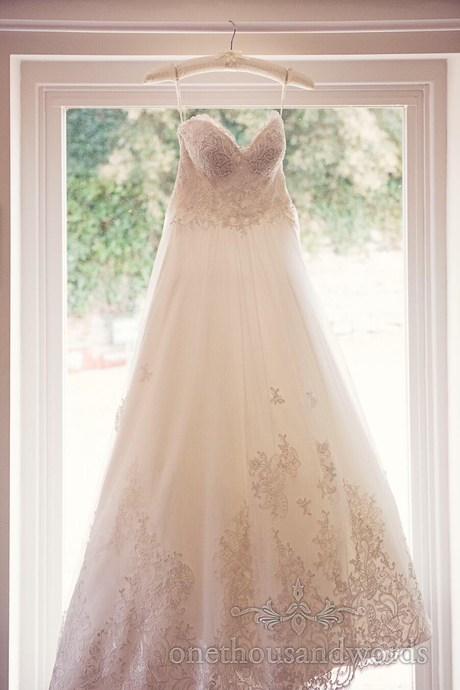 Dress hangs in window from wedding at Sopley Mill