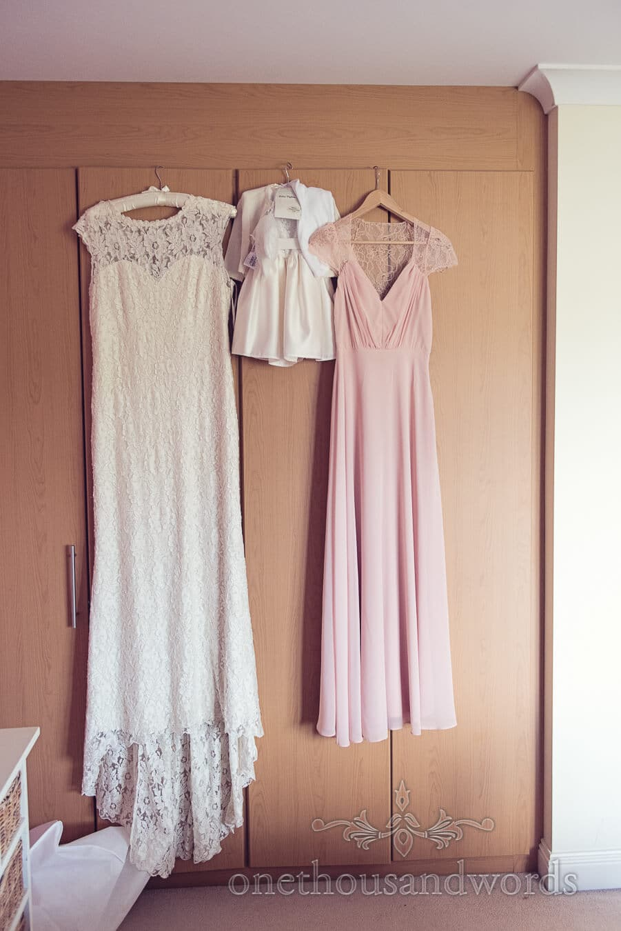 Dresses hang in bedroom before Purbeck Golf Club Wedding