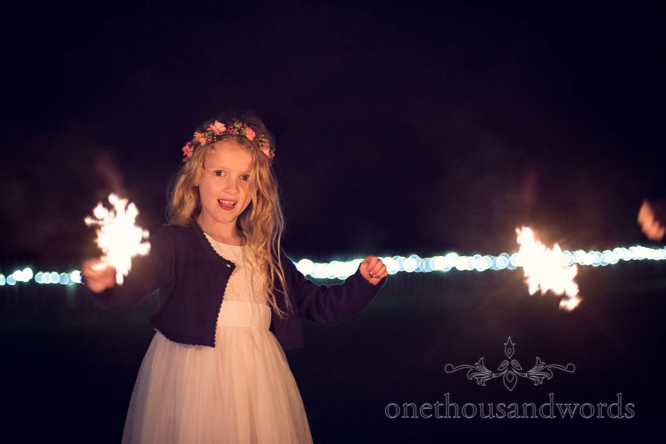 Flower girl plays with sparkler from wedding at Sopley Mill