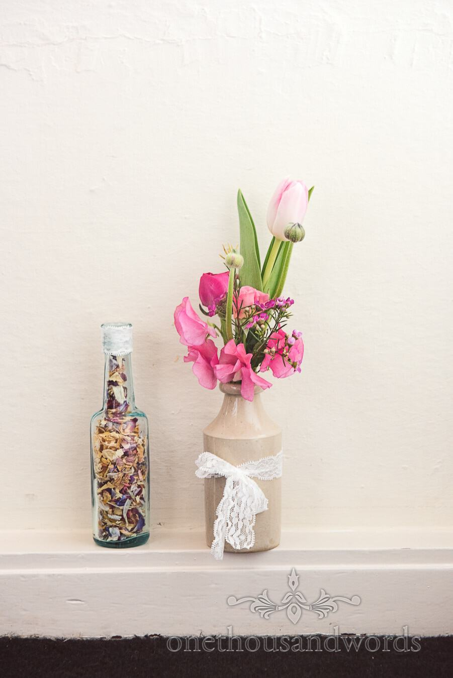 Flowers in earthenware and glass bottles wedding at Sopley Mill