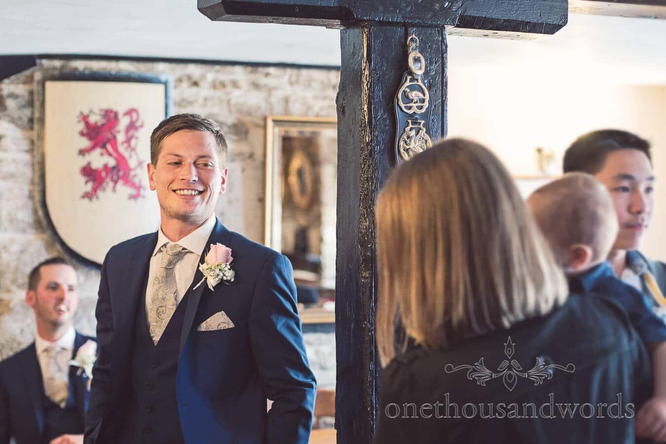 Groom smiles in pub before wedding