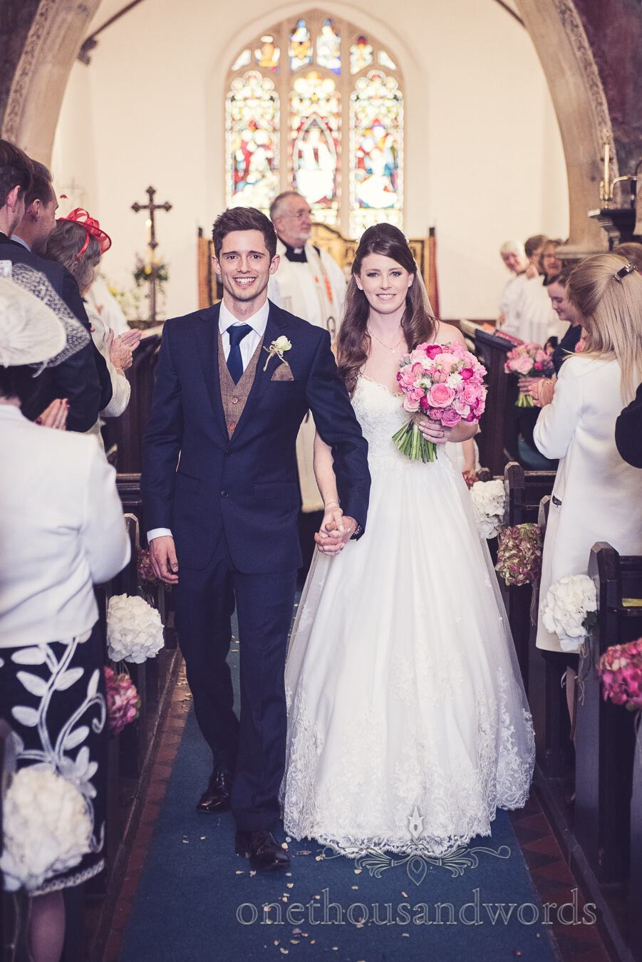Newly wed couple walk down the aisle from wedding at Sopley Mill
