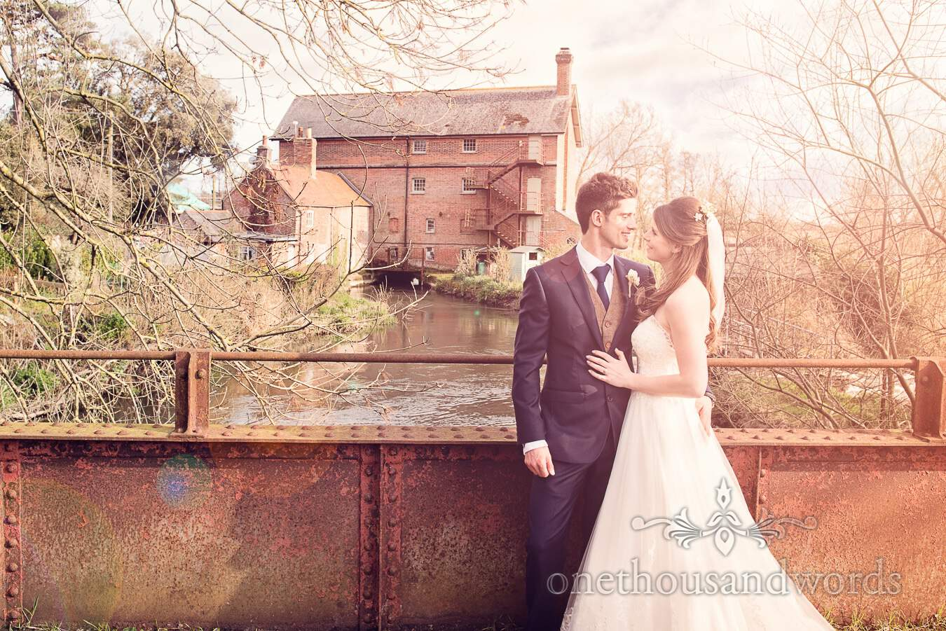Newlyweds and mill during wedding at Sopley Mill
