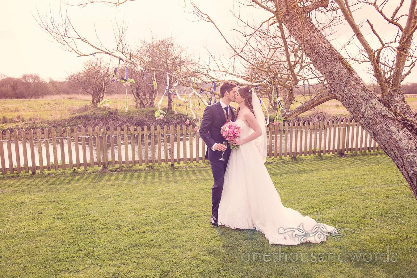 Newlyweds kiss in the garden at Sopley mill wedding