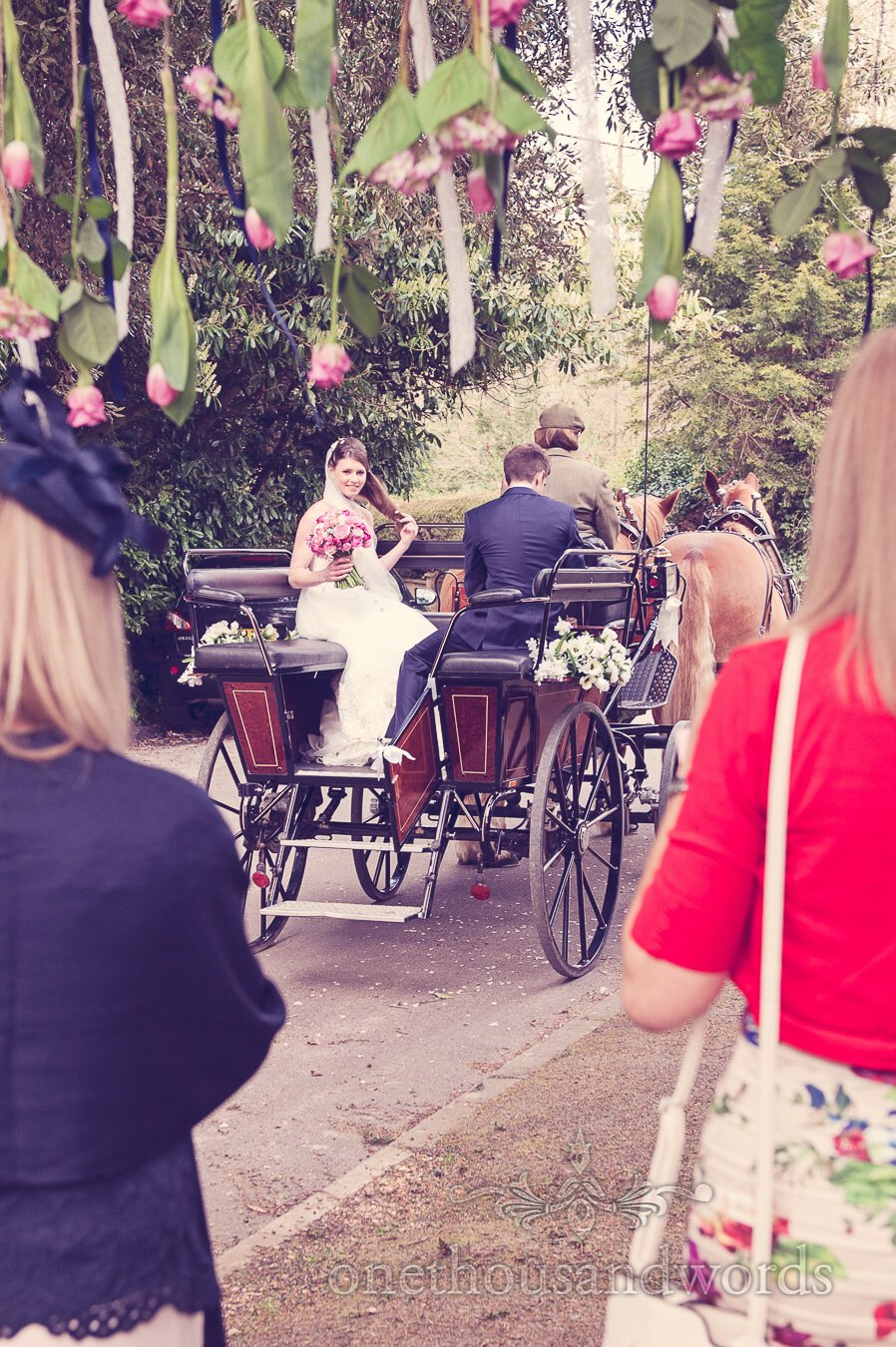 Newlyweds leave on horse drawn carriage