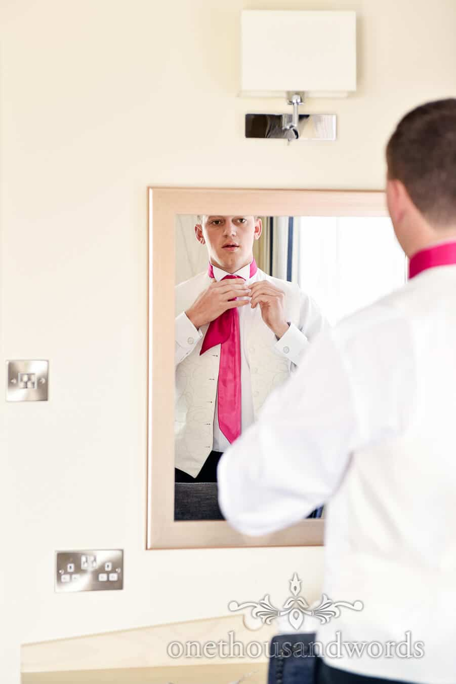 Groom adjusts pink wedding tie