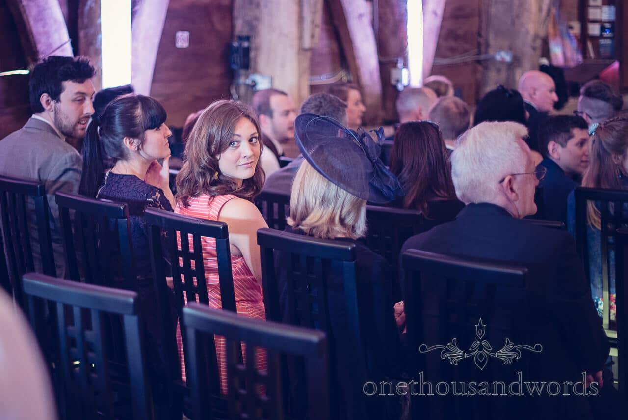 Guest looks back at bridle party entering at Barn Wedding