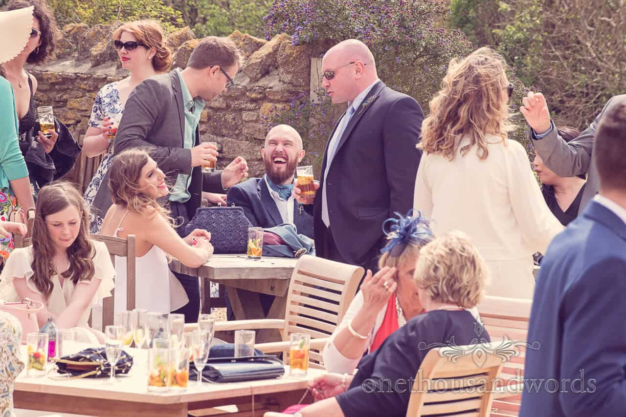 Guests enjoying drinks in the sunshine at Barn Wedding