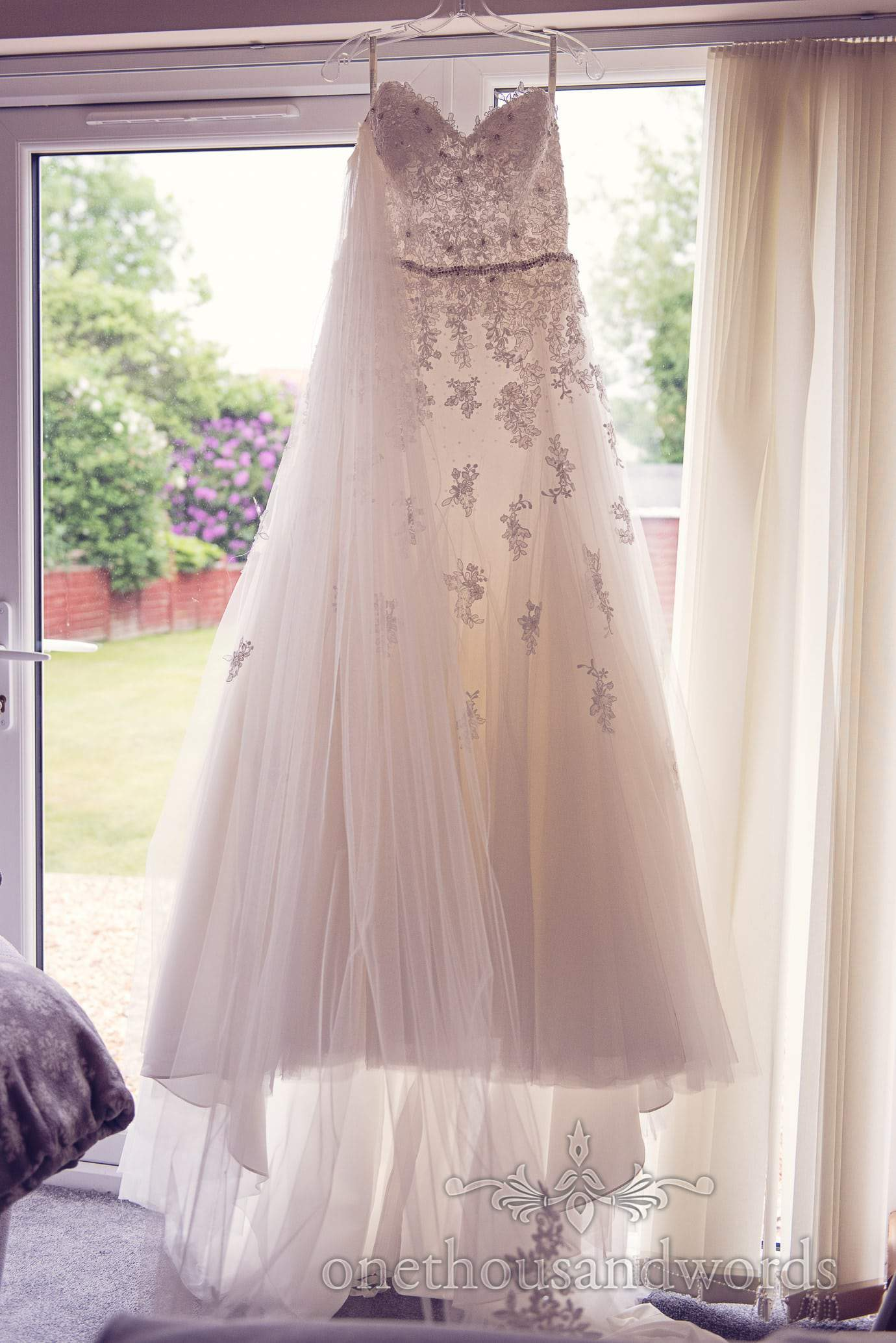 A line detailed white wedding dress hanging in window with wedding veil
