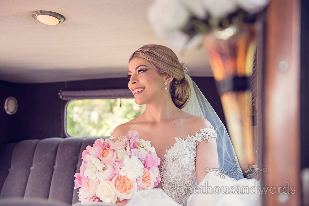 Beautiful Blonde Bride with pastel wedding bouquet in classical wedding car